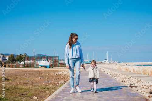 Poster Jogging mother and little daughter walking on summer beach