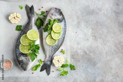 Fotografie, Obraz  two raw dorado fish with lime and parsley ready to cooking