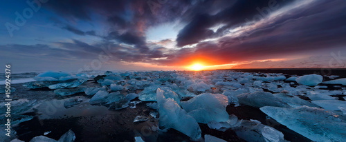 Foto op Plexiglas Nachtblauw Blue ice and sunset on the shore of Jokulsarlon, Iceland