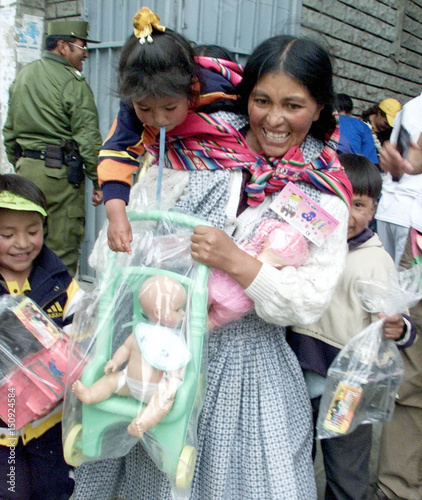 BOLIVIAN INDIAN WOMAN SMILES WITH HER CHILDREN AFTER RECEIVING GIFTS.