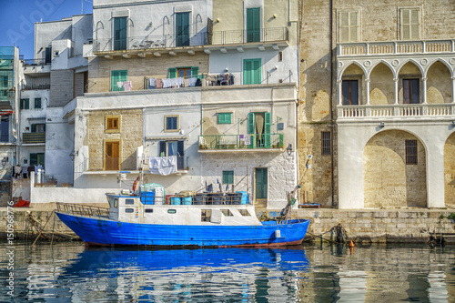 City on the water Blue boats in seaport of Monopoli, Italy