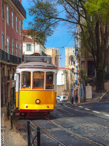Plakat Sławny rocznika koloru żółtego 28 tramwaj na ulicie Alfama, stary okręg Stary miasteczko, Lisbon, Portugalia