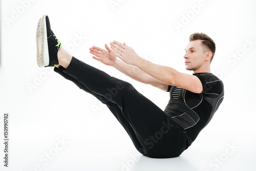 Fotografie, Obraz  Young concentrated sportsman doing abdominal exercises on the floor
