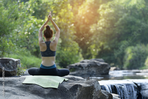 young women practicing yoga in nature near waterfall relax time.