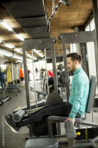 Photo sur Aluminium Voies ferrées Young man exercise on an exercise machine at the gym