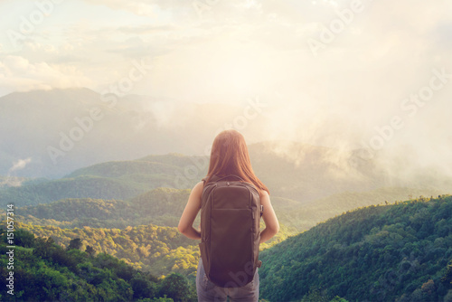 Tourist traveler concept, Young hipster girl with backpack enjoying sunset on peak mountain