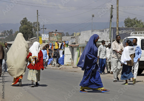 Veiled women walk along a street in the district of