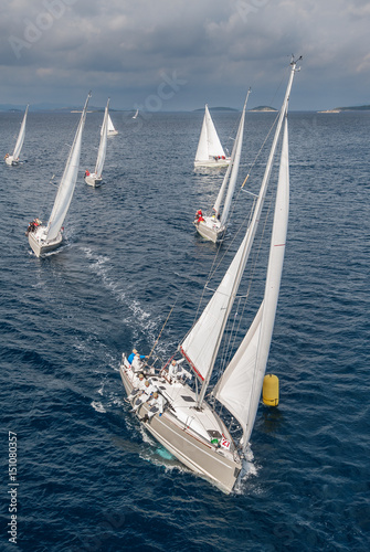 Obraz na plátně  Coming fleet of sailing boats during offshore race passing yellow buoy, bird vie