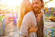 Happy smiling couple in love hug and kiss each other in the amusement park. Sunny warm spring evening