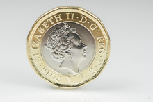 New British One Pound Sterling Coin Up Close Macro Studio Shot Against A Shiny Reflective White Background