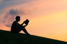 Silhouettes Of Young Man Reading A Book.