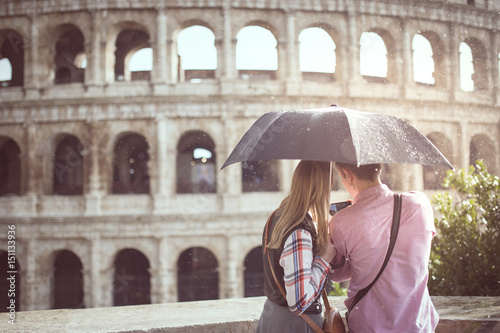 A couple with an umbrella in a rainy day, are taking pictures at the Great Roman Colosseum ( Coliseum, Colosseo ),also known as the Flavian Amphitheatre Wallpaper Mural