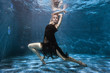 At the bottom of the pool, a woman in a dress is dancing under the water. Surrealistic photography.