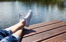 Woman's Feet Relaxing By The Waters Edge.