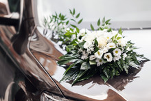 The Hood Of A Black Car Is Decorated With A Bouquet Of Flowers In A Wedding Style.