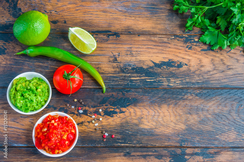 Foto op Canvas Kruiden Traditional Mexican sauces salsa and guacamole in small white bowls and fresh vegetables on the wooden rustic table, top view.