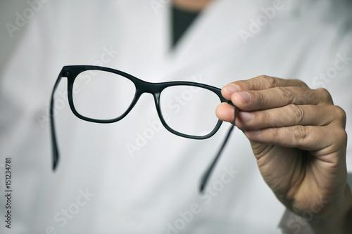 Fotomural optician man bringing a pair of eyeglasses