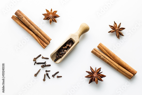 Fotografía cloves with wooden scoop and cinnamon on white