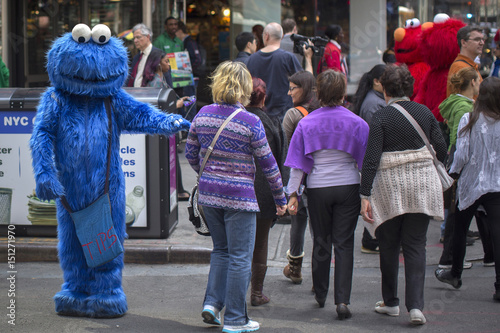 A character dressed as Cookie Monster from Sesame Street reaches out