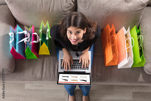 Plakat Kobieta z torby na zakupy za pomocą laptopa