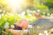 canvas print picture - Beautiful young woman lying on the field in green grass and blowing dandelion