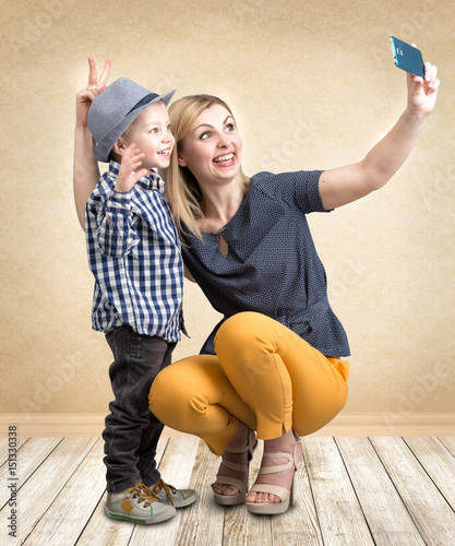 Keuken foto achterwand Retro Young mother and little son are photographed on a mobile phone making selfie.Stylish,trendy,modern