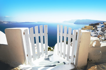 FototapetaOpen door in summer, vacation background. Oia village, Santorini, Greece, Europe location, famous and popular summer resort. White and blue color gamut photo, traditional Greek colors.
