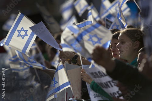 Girls wave Israeli flags at rally in support of Israel during the