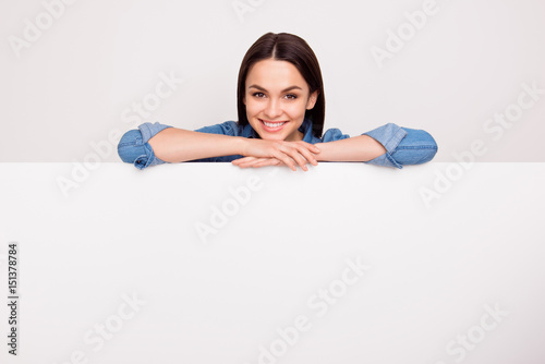 Fotografía Pretty smiling woman in jeans shirt leaning on the top of the white banner,  pla
