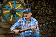 The Man Is An American With A Gun Near The Wood And Firewood In A Plaid Shirt, A Baseball Cap And Glasses Of A Stylish Appearance With Mans Accessories
