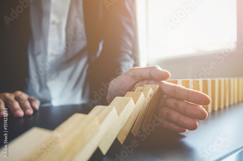 Fotografie, Obraz  Problem Solving,Close up view on hand of business woman stopping falling blocks on table for concept about taking responsibility