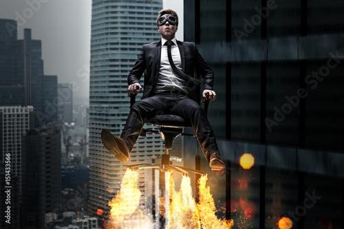 Fotografiet  Mann auf Bürostuhl mit Raketenantrieb
