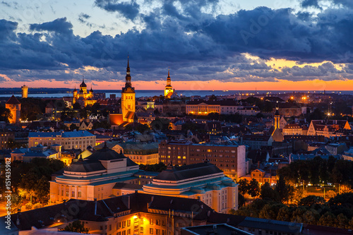 Fototapety, obrazy: TALLINN, ESTONIA - JULY, 30, 2016: Orange sunset over old town. Cathedrals towers and modern buildings aerial view.