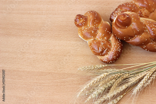 Bundle of wheat is a symbol of Jewish tradition to count the days and weeks between passover and receiving the torah on mount Sinai. Top view on wooden background
