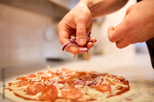 Photo Stands Pizzeria cook adding onion to salami pizza at pizzeria