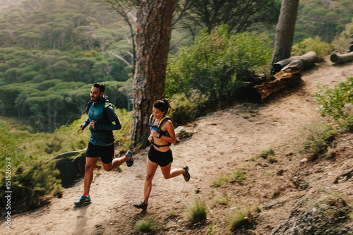 Fotografía  Young couple doing trail running workout