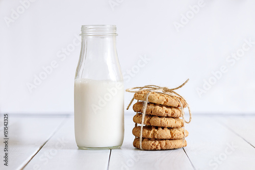 Valokuva  Biscuits with milk on wood background in the morning