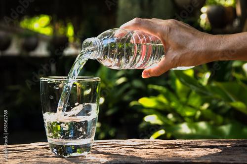 Obraz na dibondzie (fotoboard) Żeńska ręki dolewania woda od butelki szkło na natury tle