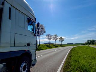 Lkw auf freier Straße / Freie Fahrt für den Lkw, vorbei an jungen Bäumen und blühenden Rapsfeldern; Sonne scheint.
