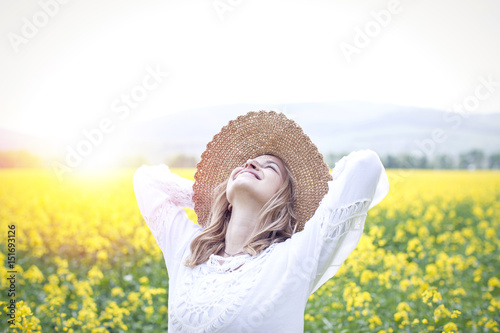 Obraz young woman in a rape field - fototapety do salonu