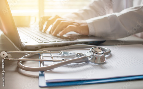 Obraz Doctor working an Laptop with Stethoscope prescription clipboard on desk in hospital medical and Healthcare of consultant from telemedicine in new treatment of patients - fototapety do salonu