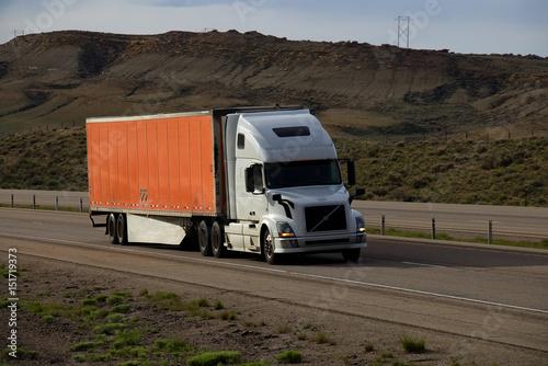 A White Volvo Semi Truck Pulls An Orange Trailer Down A Rural