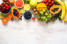 Above View Of Rainbow Colored Fruits, Strawberries, Blueberries, Mango, Orange, Grapefruit, Banana, Apple, Grapes, Kiwis On The White Background, Copy Space For Text, Selective Focus