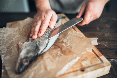 Photographie Chef hands with knife cut up fish on cutting board