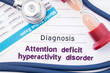 Diagnosis of Attention deficit hyperactivity disorder (ADHD). On psychiatrist table is paper with title Attention deficit hyperactivity disorder near psychiatric report, hourglass and stethoscope