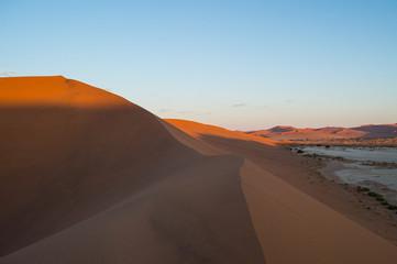 Fototapeta na wymiar Climbing Big Daddy Dune during Sunrise with View onto Salt Pan and Desert Landscape, Sossusvlei, Namibia