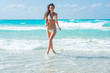 Beautiful young woman with long blond curly hair in white swimsuit run on the sand of caribbean coastline