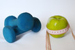 Blue dumbbells and measuring tape around green apple