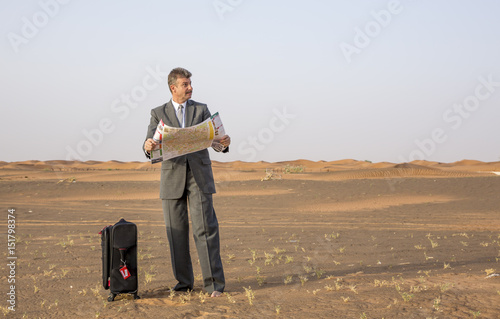 Obraz na plátně  businessman in  a desert with a suitcase, looking at a map