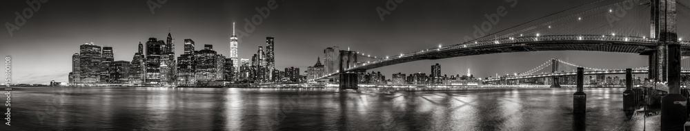 Fototapeta Panoramic Black and white view of Lower Manhattan Financial District skyscrapers at twilight with the Brooklyn Bridge and East River. New York City